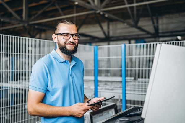 Young engeneer manager with beard checking manufactory, workplace and machinery on big factory.