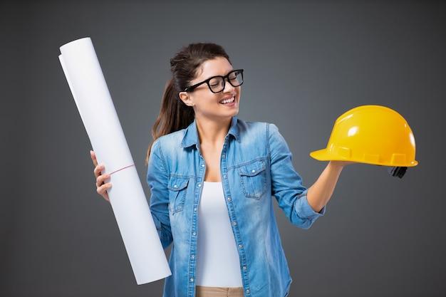 Молодой инженер. портрет улыбающейся женщины в повседневной одежде и очках, стоящей перед серой стеной и держащей чертежи для строительства и защитный шлем. работа над проектом