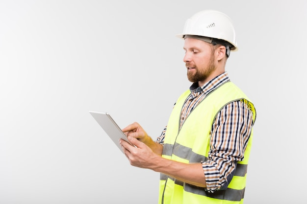 Young engineer or foreman in protective helmet and workwear pointing at display of digital tablet during presentation