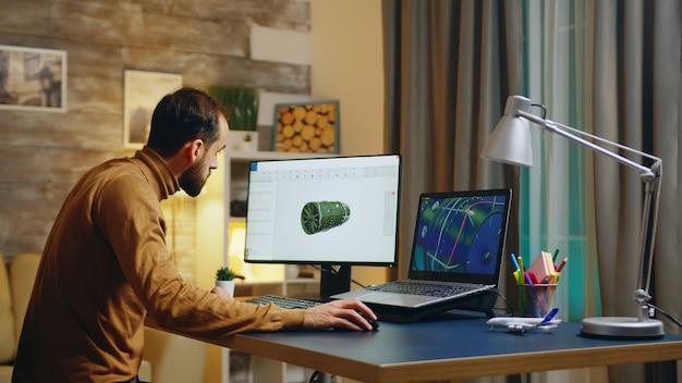 Giovane ingegnere nel suo ufficio a casa che lavora allo sviluppo di una nuova turbina. interfaccia software.