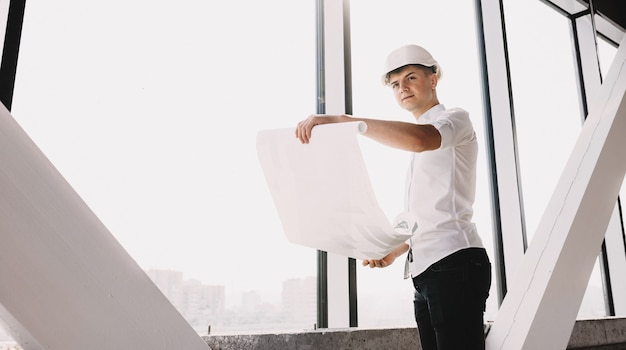 建築計画を保持し、ヘルメットで2階にポーズをとる若いエンジニア