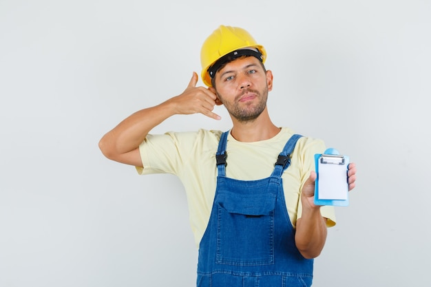 Young engineer holding clipboard with phone gesture in uniform , front view.