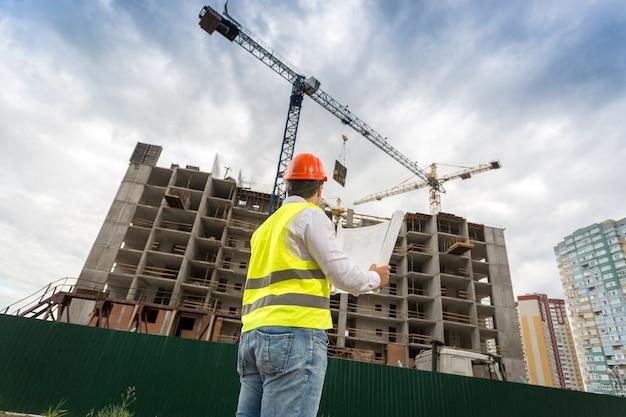 Молодой инженер в каске, глядя на строящееся здание