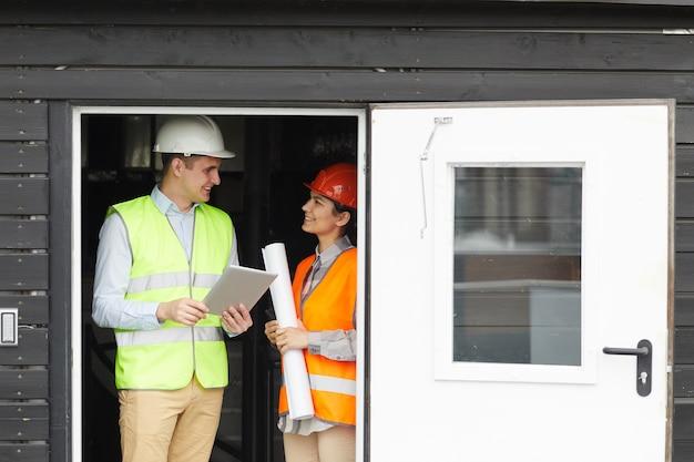 그들은 건설 현장에서 일하는 동안 여자와 이야기하는 반사 조끼에 젊은 엔지니어