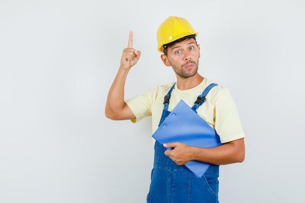 Молодой инженер в униформе, держа буфер обмена и указывая вверх, вид спереди.