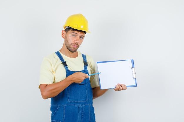 クリップボード、正面図を指している制服を着た若いエンジニア。