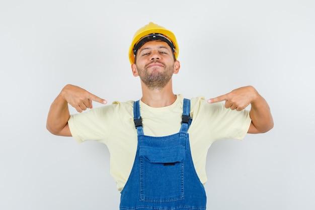 자신을 가리키고 자신감, 전면보기를 찾고 제복을 입은 젊은 엔지니어.