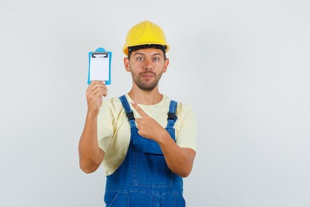 Молодой инженер в форме, указывая на мини-буфер обмена, вид спереди.