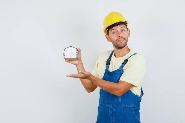 Молодой инженер в униформе показывает модель дома и смотрит внимательно, вид спереди.