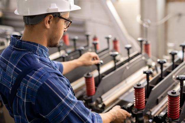作業領域で操作しながら産業用機械のそばに立っている白いヘルメットの若いエンジニア