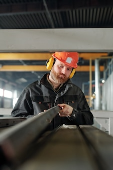 Young engineer of industrial plant looking at one of iron details while examining its characteristics by workplace