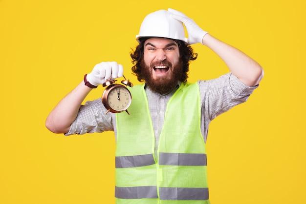젊은 엔지니어가 시계를 들고 머리 위로 손을 들고 카메라에 매우 스트레스를 받고 있습니다.
