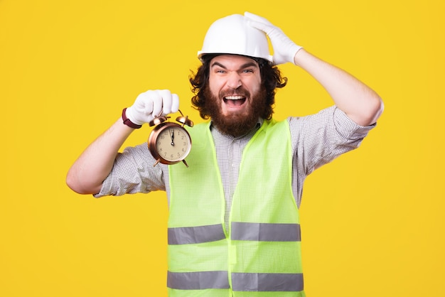Young engineer is holding a clock and with a hand above his head is looking very stressed at the camera