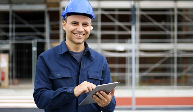 Young engineer man in suit and helmet working on tablet pc and smiling