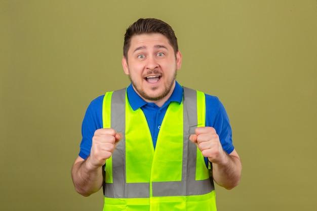 Молодой инженер человек в строительном жилете, сжимая кулаки, выглядит удивленным, улыбаясь, стоя с счастливым лицом на изолированном зеленом фоне