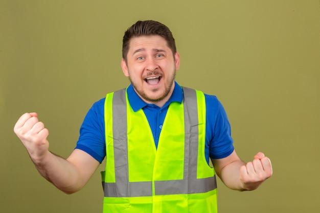 Молодой инженер человек в строительном жилете, сжимая кулаки, улыбаясь, стоя со счастливым лицом, празднует концепцию победителя на изолированном зеленом фоне