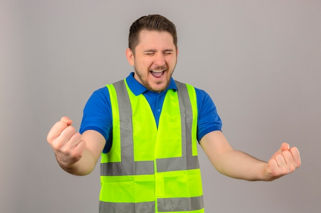 Молодой инженер человек в строительном жилете, сжимая кулаки, улыбаясь, стоя со счастливым лицом, празднует концепцию победителя на изолированном белом фоне