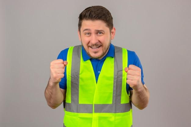 Giovane ingegnere uomo che indossa la costruzione giubbotto stringendo i pugni sorridenti in piedi con la faccia felice su sfondo bianco isolato