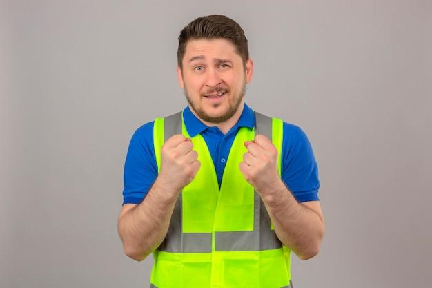 Молодой инженер человек в строительном жилете, сжимая кулаки, улыбаясь, стоя с счастливым лицом на изолированном белом фоне