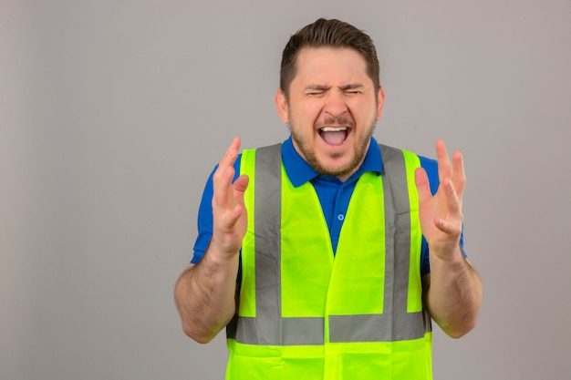 Молодой инженер человек в строительном жилете сумасшедший и безумный кричит и кричит с агрессивным выражением лица и руками, поднятыми над изолированным белым фоном