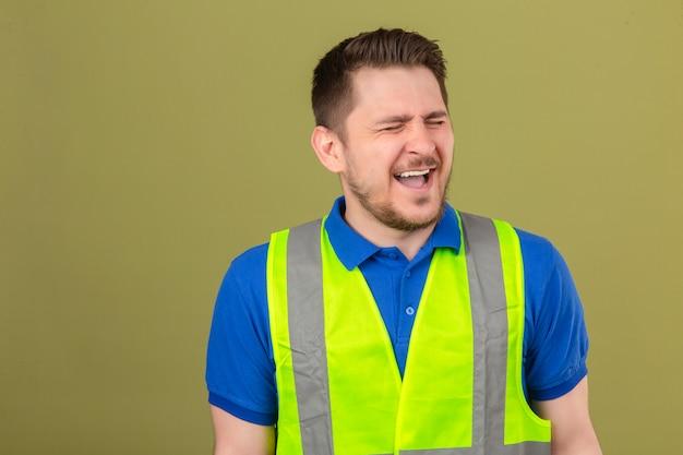 Молодой инженер в строительном жилете сумасшедший и безумный кричит и кричит с агрессивным выражением лица на изолированном зеленом фоне