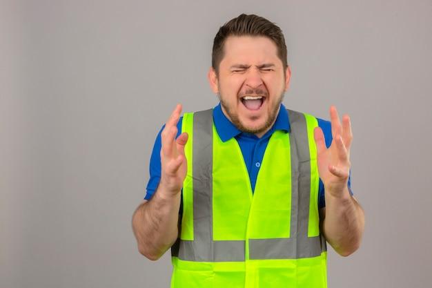 Giovane ingegnere uomo che indossa la costruzione giubbotto pazzo e pazzo gridando e urlando con espressione aggressiva e braccia alzate su sfondo bianco isolato