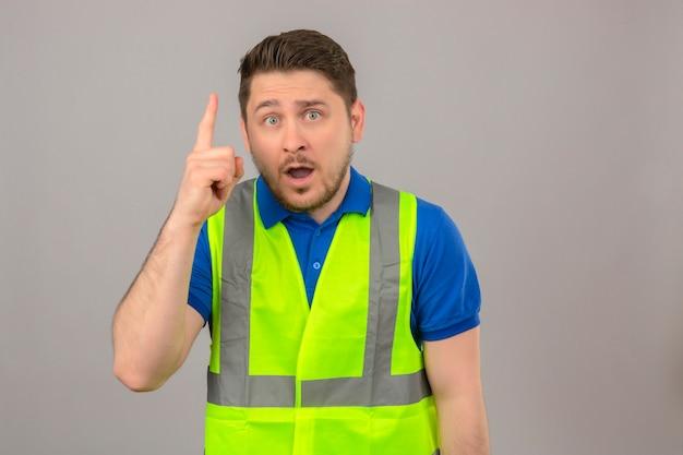 Молодой инженер человек в строительном жилете выглядит удивленным, указывая пальцем вверх, имея новую идею на изолированном белом фоне