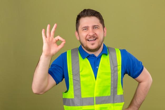Молодой инженер человек в строительном жилете, глядя в камеру, улыбаясь, веселый, делая хорошо, знак, стоящий на изолированном зеленом фоне