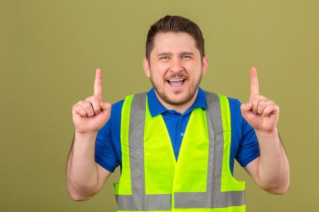 Молодой инженер человек в строительном жилете, глядя в камеру, улыбаясь, весело указывая пальцами на изолированный зеленый фон