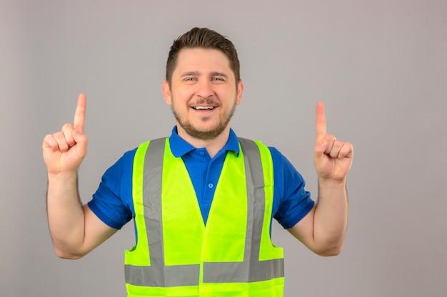 Молодой инженер человек в строительном жилете, глядя в камеру, улыбаясь, весело указывая пальцами на изолированном белом фоне