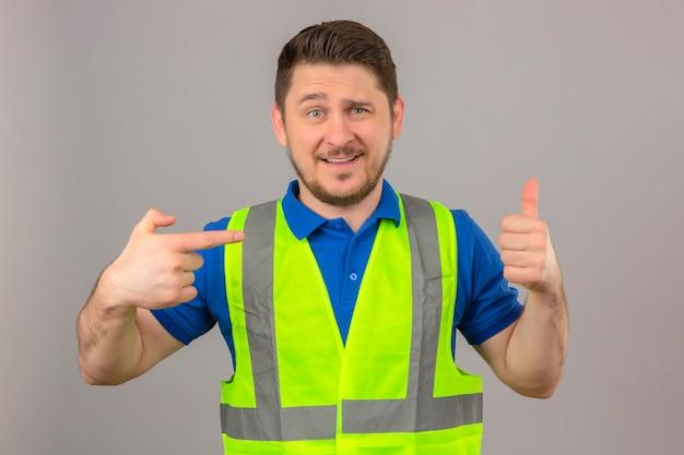 Молодой инженер человек в строительном жилете смотрит в камеру, весело улыбаясь, показывая большой палец вверх, указывая пальцем, стоящим на изолированном белом фоне