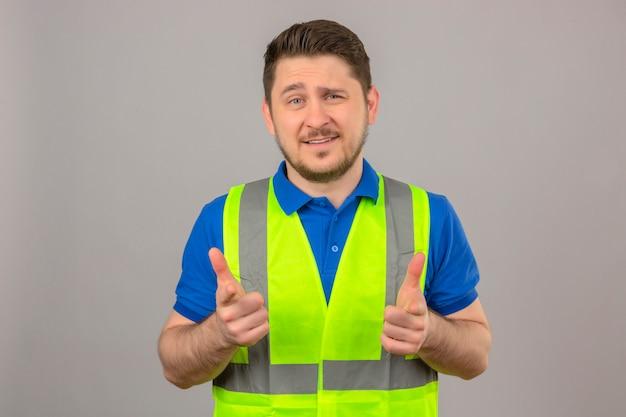 Молодой инженер человек в строительном жилете смотрит в камеру, улыбаясь, указывая пальцами на камеру на изолированном белом фоне