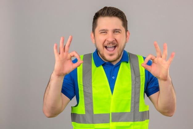 Молодой инженер человек в строительном жилете, глядя в камеру с большой улыбкой и счастливым лицом, делает хорошие знаки на изолированном белом фоне