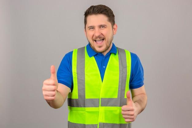 Молодой инженер человек в строительном жилете, глядя в камеру с большой улыбкой и счастливым лицом, показывает палец вверх на изолированном белом фоне