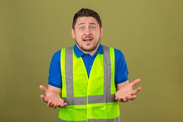 Молодой инженер человек в строительном жилете выглядит невежественным и смущенным, сомневаясь в изолированном зеленом фоне