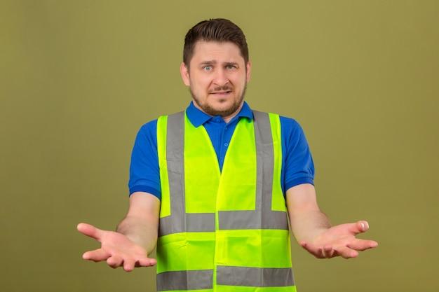 Молодой инженер человек в строительном жилете выглядит смущенным, стоя с руками и руками, поднятыми на изолированном зеленом фоне