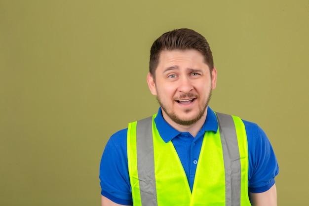 Молодой инженер человек в строительном жилете выглядит смущенным с выражением лица, задающим вопрос на изолированном зеленом фоне
