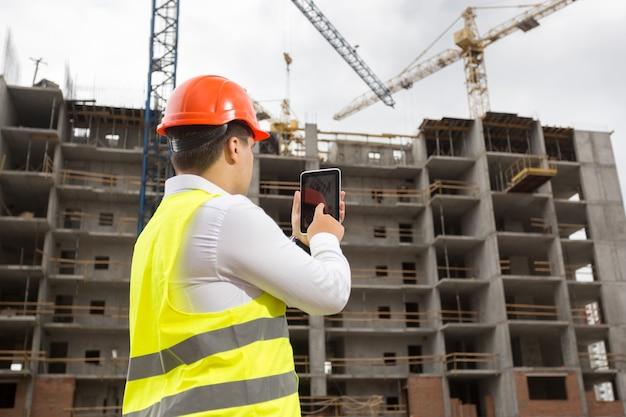 Молодой инженер на строительной площадке с цифровым планшетом
