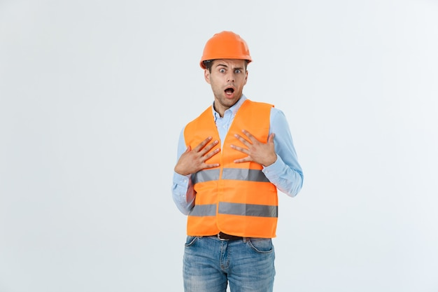 Young engineer opens his mouth shocked looking away, isolated on a white background.