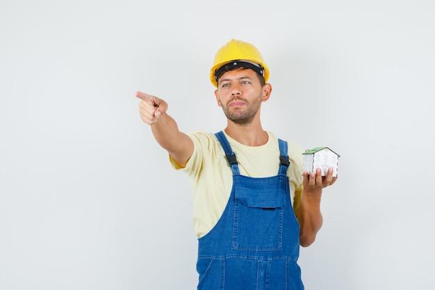Молодой инженер указывая прочь и держа модель дома в едином виде спереди.