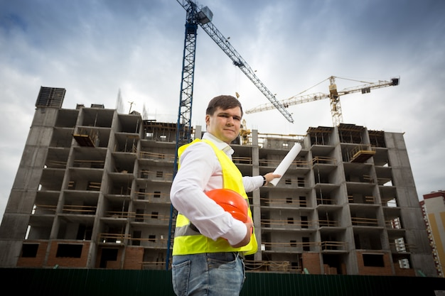Young engineer in safety vest with blueprints at building site