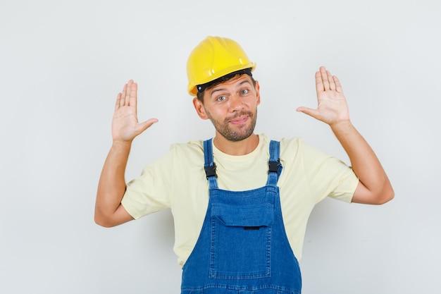 Giovane ingegnere che mostra le palme in gesto di resa in uniforme e guardando allegro, vista frontale.
