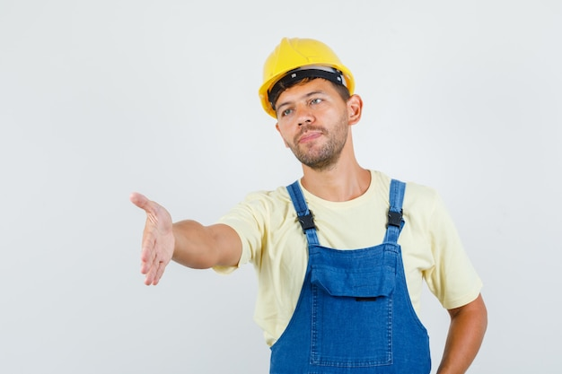 Молодой инженер протягивает руку для тряски в форме спереди.