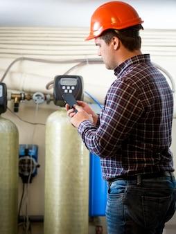 공장에서 산업용 펌프에서 미터 판독 값을받는 젊은 엔지니어