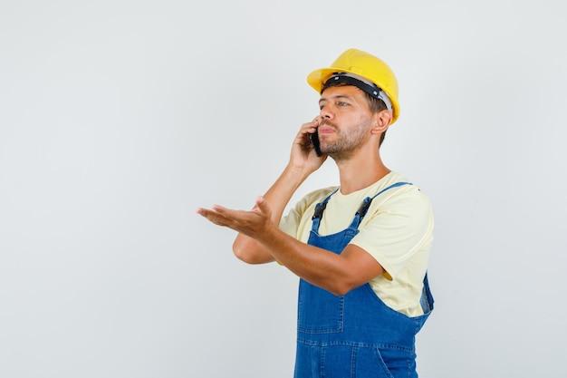 制服を着て、物思いにふける、正面図で開いた手のひらで電話で話している若いエンジニア。