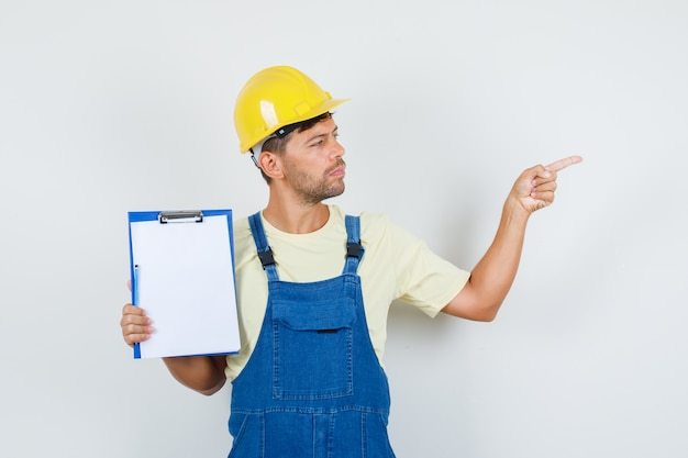 Young engineer in uniform holding clipboard and pointing to side , front view.
