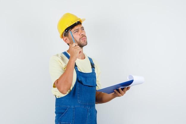 Giovane ingegnere in uniforme che tiene matita e appunti e guardando pensieroso, vista frontale.