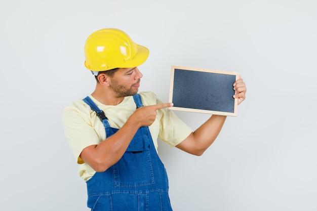 Giovane ingegnere in uniforme che punta alla lavagna e guardando concentrato, vista frontale.