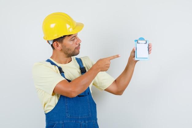 Giovane ingegnere in uniforme che punta a mini appunti e che sembra concentrato, vista frontale.