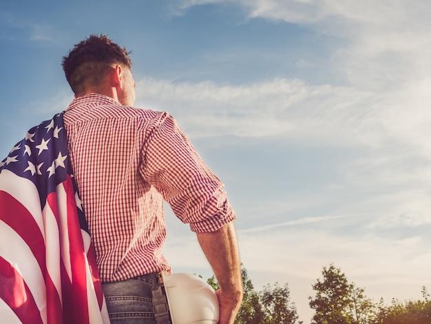 若いエンジニア、白いヘルメット、アメリカの国旗